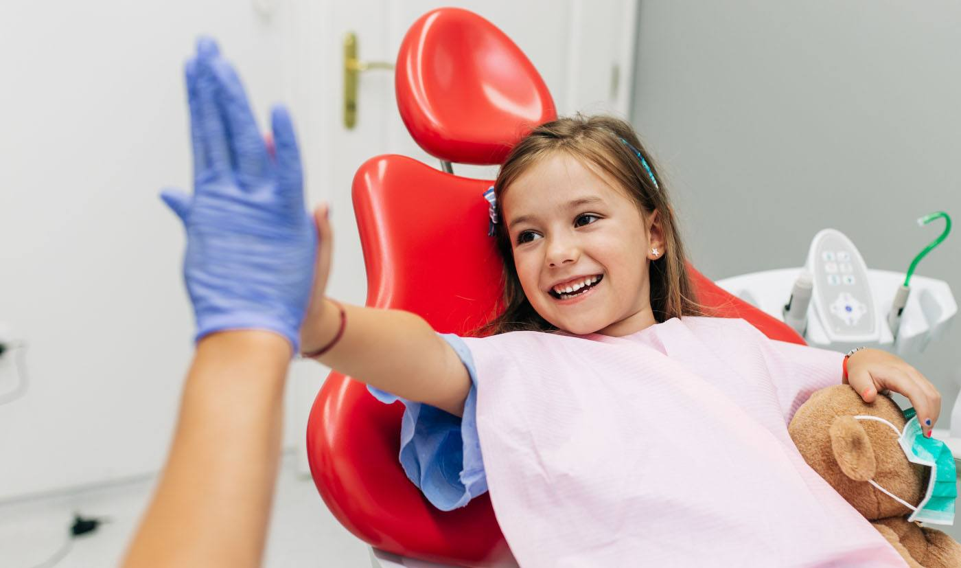 young girl giving dentist high-five